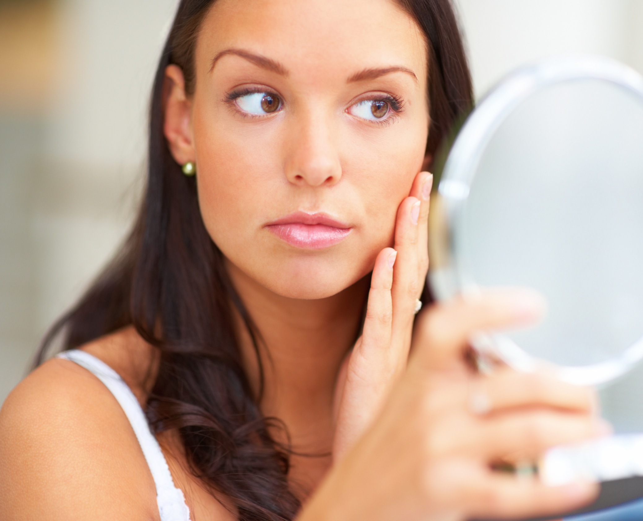 Woman-looking-at-her-face-in-mirror